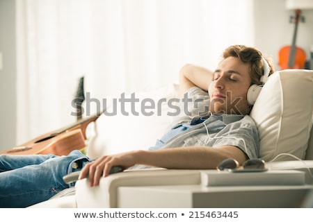 Man lying down on sofa and relaxing Stock photo © HASLOO