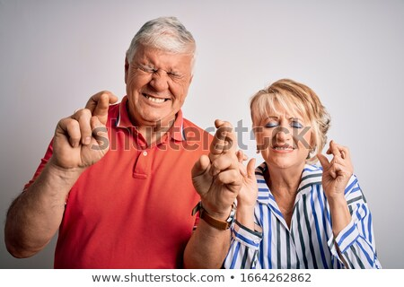 Senior man standing with finger crossed for luck Stock photo © bmonteny