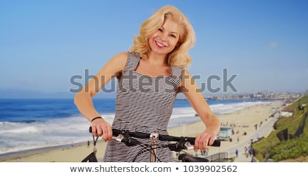 Beautiful blonde in white sundress on bike ride at the beach Stock photo © wavebreak_media