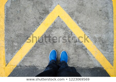 standing above arrow shaped sign on the road top view stock photo © stevanovicigor
