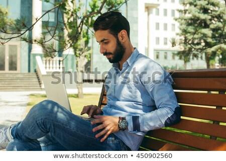 Afrikai derűs férfi laptop ül fából készült Stock fotó © deandrobot