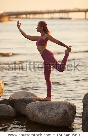 beautiful young woman standing near big stone on the beach and l Stock photo © Massonforstock