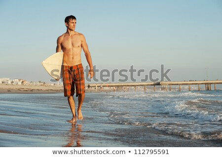 Young shirtless man holding surfboard at beach on sunny day Stock photo © wavebreak_media