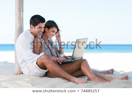 Couple on beach with laptop computer Stock photo © IS2