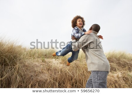 homem · saltando · praia · sorridente · mar · inverno - foto stock © is2