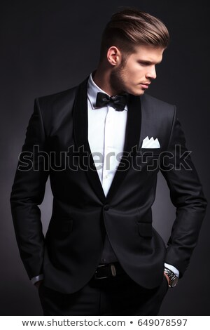 young man in tuxedo looks to side while holding collar stock photo © feedough