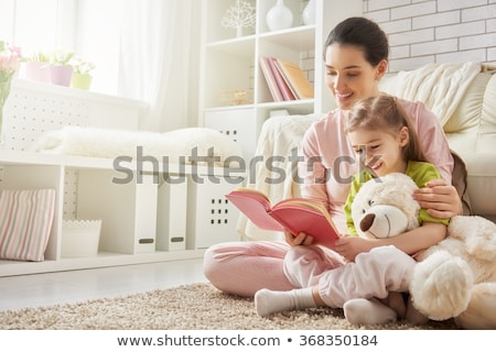 a mom reading a book to children stock photo © bluering
