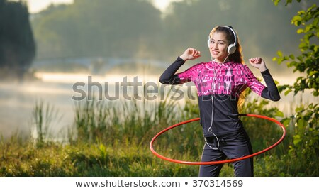 A girl doing hula hoop at the park Stock photo © bluering