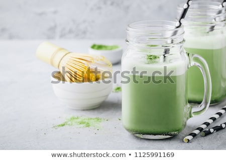 Green tea latte with ice in mason jar, matcha powder and candy made of matcha on wooden background.  Stok fotoğraf © galitskaya