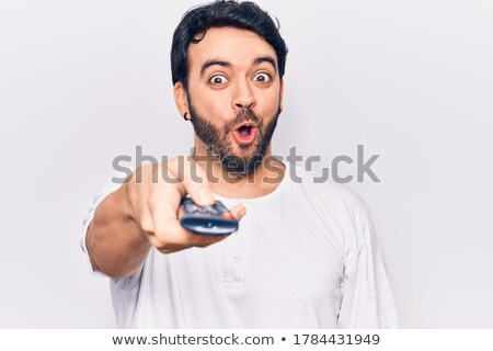 portrait of a shocked young man holding tv remote control stock photo © deandrobot