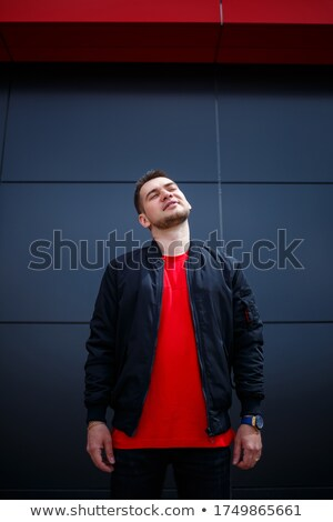 Young and beautiful man in basic t-shirt smiling and speaking on Stock photo © deandrobot