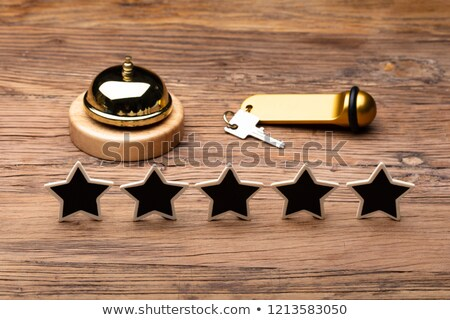 five star service bell and hotel key on wooden desk stock photo © andreypopov