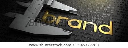 Business Concept with Golden Word BRAND on Black Background and Vernier Caliper. Stock photo © tashatuvango