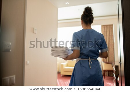 Back view of young chamber maid in uniform carrying stack of clean white towels Stock photo © pressmaster