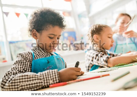 cute african schoolboy in blue apron using highlighter while drawing at lesson stock photo © pressmaster