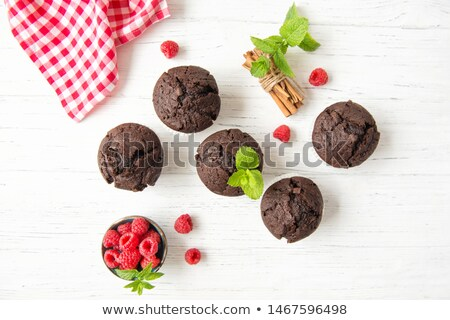 Fresh dark chocolate muffin with mint leaves on rustic wooden ta Stock photo © marylooo