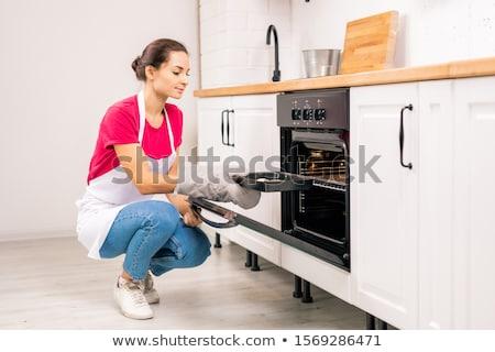 Jovem dona de casa avental bandeja bolinhos Foto stock © pressmaster