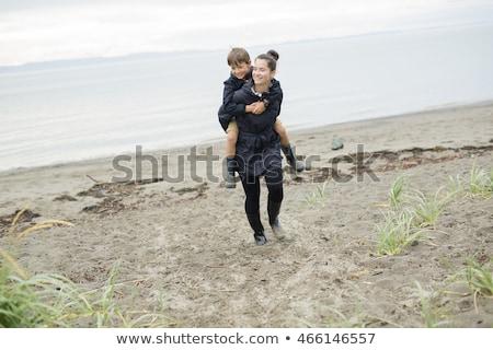 Family Enjoying The Rain And Having Fun Outside On The Beach A Gray Rainy Foto stock © Lopolo