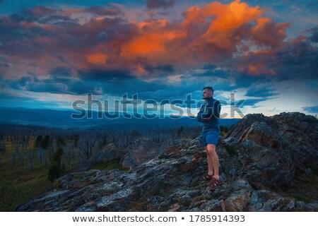 Homem em pé topo penhasco fantástico pôr do sol Foto stock © olira