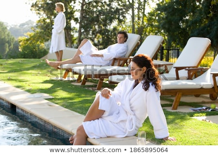 blond woman resting next to swimming pool stock photo © photography33