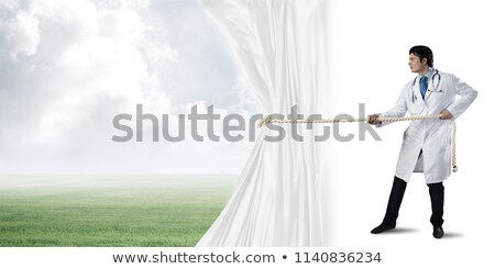 Hands pulling rope over dark background Stock photo © artfotoss