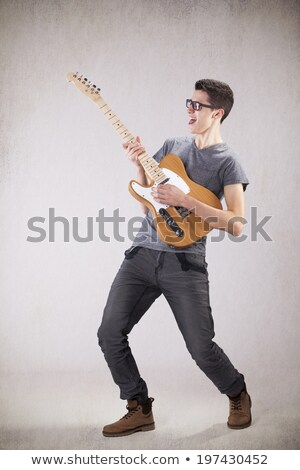 Concntrated young male guitarist playing electric guitar and using amplifier Stock photo © deandrobot