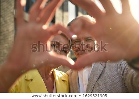 Pár szeretet készít szív alak kezek kint Stock fotó © photocreo