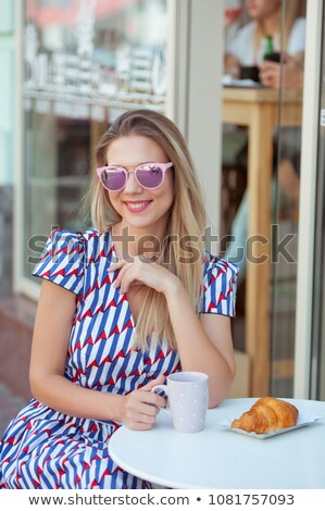 beautiful young woman sitting at the cafe table stock photo © deandrobot
