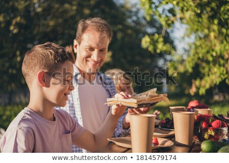 Young boy at party sitting at table with a sandwich smiling Stock photo © monkey_business