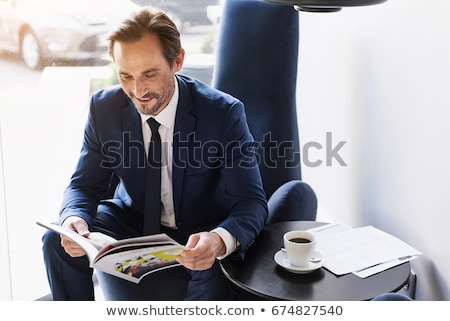 successful caucasian businessman reading magazine stock photo © rastudio