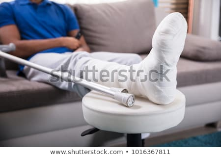 Stock photo: African-american man with broken leg and crutches.