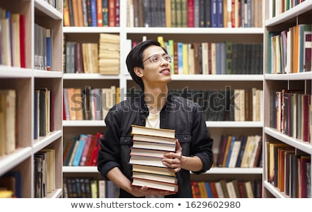 Portrait of a smiling young school nerd guy holding book Stock photo © deandrobot