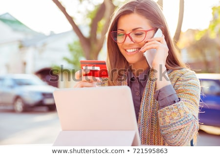 Young business woman using mobile phone holding credit card. Stock photo © deandrobot