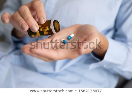 fiatal · nő · elvesz · gyógyszer · beteg · fürdőköpeny · tabletták - stock fotó © feverpitch