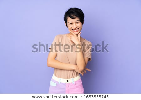 Happy asian woman posing isolated over puple wall background showing display of laptop computer. Stock photo © deandrobot