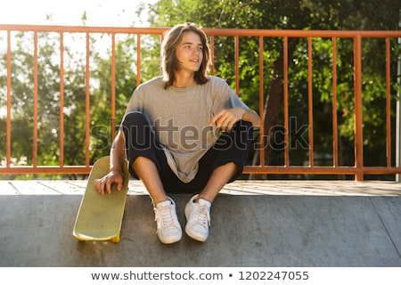 Photo of joyful guy 16-18 in casual wear sitting on ramp in skat Stock photo © deandrobot
