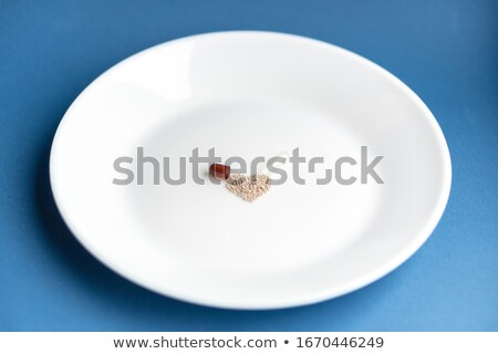Heart made from medicine pills and capsules on a white plate on a blue background, copy space. Color Stock photo © artjazz