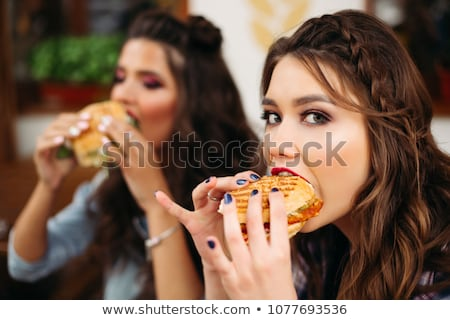 Girl with bright make-up taking a bite of burger. Stock photo © studiolucky