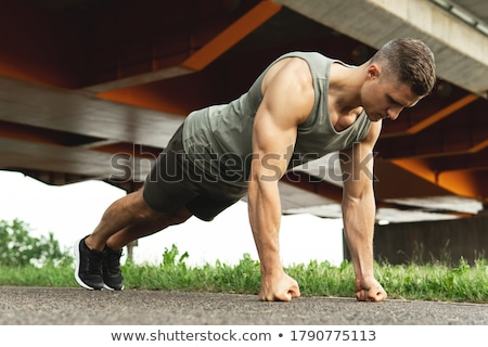 adult man training chest muscles doing calisthenics workout outdoors stock photo © diego_cervo