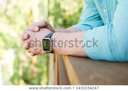 Hands of restful man with wristwatch leaning against wooden banisters Stock photo © pressmaster