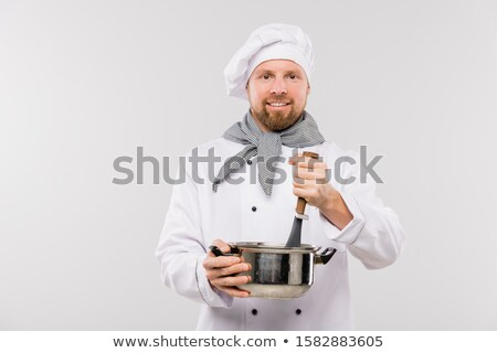 Professional male chef mixing soup or other meal in pan while cooking food Stock photo © pressmaster
