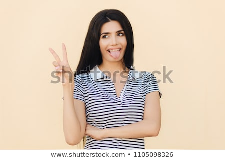 Positive funny female makes peace sign with hand, shows tongue, being in good mood, has long dark ha Stock photo © vkstudio