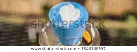 Trendy drink: Blue latte. Top view of hot butterfly pea latte or blue spirulina latte on gray textur Stock photo © galitskaya