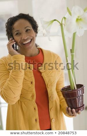 femme · noire · téléphone · portable · pot · à · fleurs · souriant · jeunes - photo stock © Edbockstock