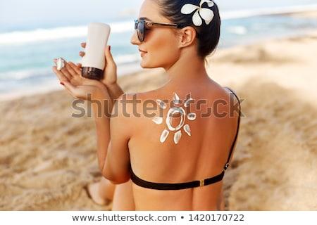 woman in bikini holding suncream at the beach Stock photo © mangostock