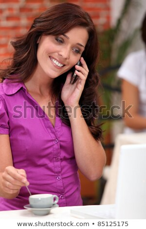 Woman on a cellphone while stirring an expresso in a restaurant Stock photo © photography33