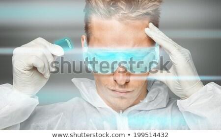 young man inserting a sd card into his head stock photo © konradbak
