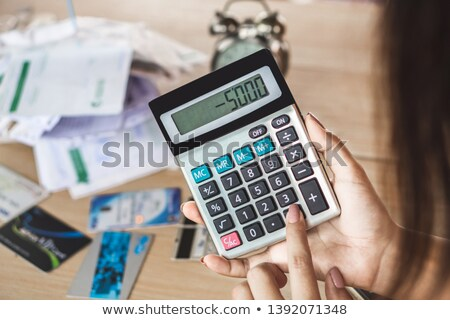 Businesswoman Holding Calculator At Desk stock photo © AndreyPopov