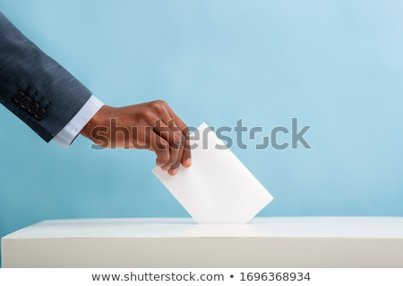 man putting a ballot into a voting box   usa stock photo © zerbor