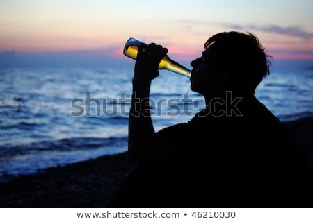 teenager boy opens beer bottler on stone seacoast in evening Stock photo © Paha_L